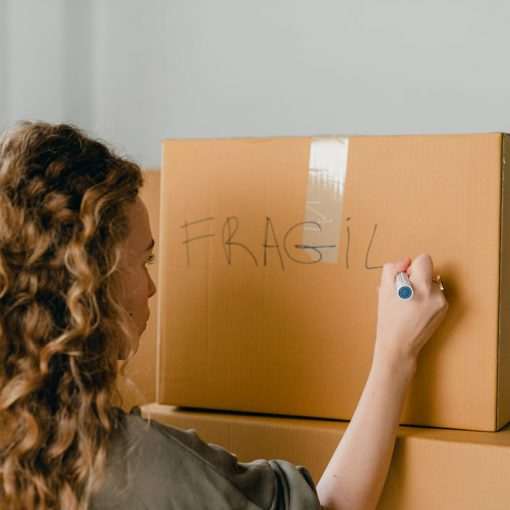 unrecognizable woman writing note on carton box with marker