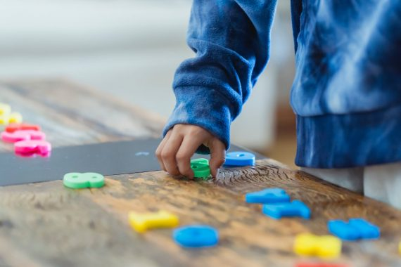 ethnic kid making row of toy numbers