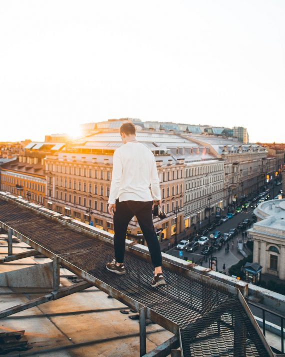 man in white long sleeve shirt and black pants standing on top of a building during